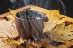 Van de koffiekop en herfst bladeren op een houten lijst Stock Foto