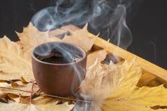 Van de koffiekop en herfst bladeren op een houten lijst Royalty-vrije Stock Afbeeldingen