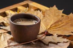 Van de koffiekop en herfst bladeren op een houten lijst Stock Fotografie