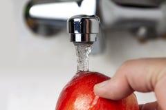 Van de kraan giet water op Apple royalty-vrije stock afbeeldingen