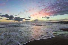 Van de kust met nat zand, overzees met golven, bergen is er een fantastische mening van zonsonderganghemel Plaatseiland Kreta, Gr royalty-vrije stock afbeelding
