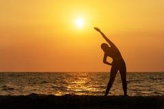 Van de de levensstijlmening van de oefeningsgeest de vitaliteit van de de vrouwenvrede, silhouet in openlucht op de Overzeese zon stock afbeelding