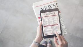 Van de persoonsholding en lezing nieuws van tablet stock afbeeldingen