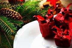 Van de plaat rode giften van close-upkerstmis de pijnbomen houten oppervlakte Stock Foto's