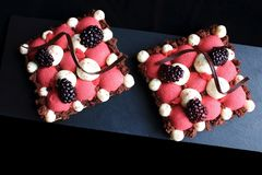 Van de rode aalbesmousse en braambes bladerdeegdesserts met geranseld ganache en chocolade spiraalvormige decoratie, hoogste meni stock afbeeldingen