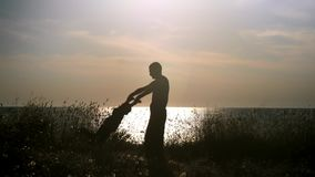 Van de silhouet het gelukkige vader en zoon spelen op het strand bij zonsondergang Papa die zijn kindhanden houden die hem rond s