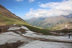 Van de de sneeuw blauwe hemel van het bergen de groene gras witte witte wolken stock foto's