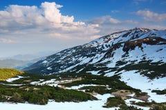 Van de sneeuw opent het behandelde gazon een mening van groen gras, hooggebergte met de pieken in sneeuw Hemel met wolken De zonn stock afbeelding