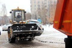 Van de de sneeuwverwijdering van de stadsdiensten het speciale materiaal na sneeuwval stedelijke nut De tractor laadt sneeuw in d stock foto