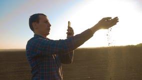 Van de de spruitwetenschapper van de mensenlandbouwer de onderzoekersbeelden op de smartphonegrond de landbouwer houdt de grond i stock video