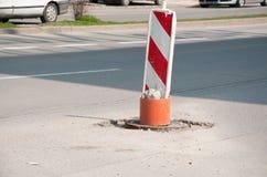 Van de straatwederopbouw of bouw barricade behandelt het voorzichtigheids rode en witte teken het open gat van mangat op de weg a stock fotografie