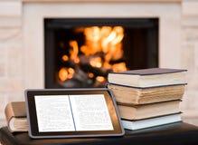 Van de tabletcomputer en stapel boeken op de achtergrond van de open haard royalty-vrije stock afbeelding