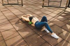 Van de themasport en rehabilitatie sportengeneeskunde De mooie sterke slanke Kaukasische vrouwenatleet gebruikt het groene gebied royalty-vrije stock afbeeldingen