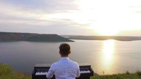Van de twee musicipianist en accordeonist het spelen op de rotsen bij zonsondergang over overzees stock videobeelden