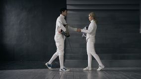 Van de twee schermersman en vrouw schokhanden elkaar aan het eind van het schermen de concurrentie binnen Stock Fotografie