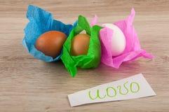 Van de Uovotitel en kip eieren in document die op houten lijst leggen Stock Afbeeldingen