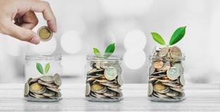 Van de van het besparingsgeld, Bankwezen en Investering concepten, Hand die muntstuk in glasflessen zetten met installaties het g stock fotografie