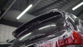 Van de de wasauto ` s van de mensenarbeider de legeringswielen op een autowasserette Autowasserettewas de auto bij de autowassere royalty-vrije stock fotografie