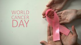 4 van de wereldkanker van februari de daginschrijving, mensenhanden die roze lint houdt stock videobeelden