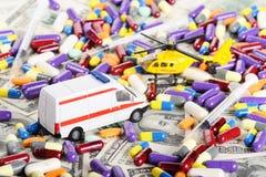 Van de ziekenwagenauto en helikopter speelgoed door dollars en pillen Royalty-vrije Stock Foto's