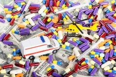 Van de ziekenwagenauto en helikopter speelgoed door pillen en dollars Royalty-vrije Stock Afbeeldingen
