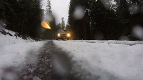 Van Drives By in Slush and Snow in the Rain. Low angle view of a van driving by headlights on in the cold weather stock footage
