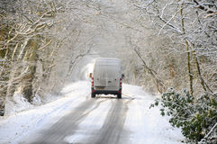Van driving along snow covered country lane Royalty Free Stock Images
