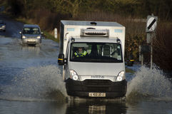 Van driving through floodwaters England UK. UK Felmersham -- 10 Jan 2014 -- Motorists negotiate a flooded road next to the Great River Ouse at Felmersham in Stock Photos