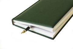 Van een gesloten agenda, kunt u de vulpen op witte bac zien Stock Foto's