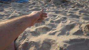 Van een man hand giet zand op het strand stock videobeelden