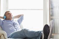Van gemiddelde lengte van de ontspannen mens die Op middelbare leeftijd aan muziek thuis luisteren Stock Afbeeldingen