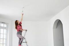 Van gemiddelde lengte van vrouw op ladder die gloeilamp in nieuw huis passen stock foto