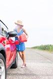 Van gemiddelde lengte van vrouwen bijtankende auto bij de landweg tegen duidelijke hemel Stock Afbeelding