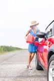 Van gemiddelde lengte van vrouwen bijtankende auto bij de landweg tegen duidelijke hemel Stock Foto