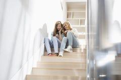 Van gemiddelde lengte van zusters die aan muziek op trap luisteren Stock Fotografie