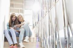 Van gemiddelde lengte van zusters die aan muziek op trap luisteren Stock Afbeeldingen