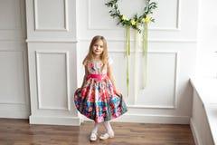 Van gemiddelde lengte van weinig glimlachend meisjeskind in het kleurrijke kleding binnen stellen royalty-vrije stock afbeelding