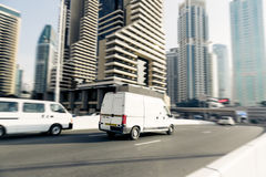 Van Going Fast. Dubai skyscrapers in the background. panning shot with motion blur Stock Image