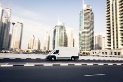 Van Going Fast. Dubai skyscrapers in the background. panning shot with motion blur Stock Photo
