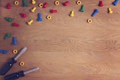 Van het achtergrond jonge geitjesspeelgoed Kaderpensionair met kleurrijke noten, bouten en twee schroevedraaiers op houten lijst  Royalty-vrije Stock Foto