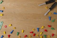 Van het achtergrond jonge geitjesspeelgoed Kaderpensionair met kleurrijke stuk speelgoed hulpmiddelen op houten lijst Hoogste men Stock Fotografie