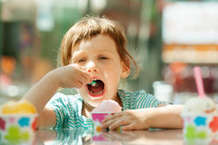 3 van het babyjaar meisje die roomijs eten bij openluchtkoffie Stock Afbeeldingen