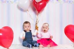 Van het babyjongen en meisje het spelen met harten Stock Afbeelding