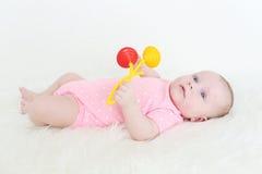 3 van het babymaanden meisje met rammelaar Stock Foto