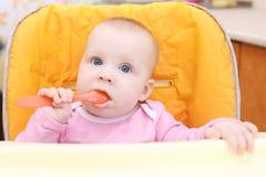 7 van het babymaanden meisje op babystoel in keuken met lepel Royalty-vrije Stock Fotografie