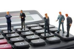 Van het bedrijfs stuk speelgoed geïsoleerdet mens op calculator royalty-vrije stock fotografie
