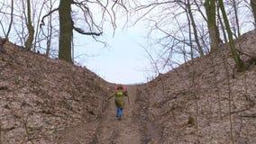 Van het bos aan de heuvel, looppas uit, neemt een tiener in een jasje, met een stok in zijn hand, te voet zoals een reiziger toe stock footage