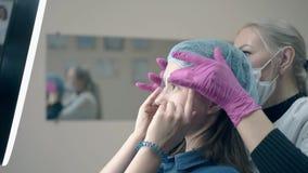 Van het Browmeester en meisje controle permanente make-up met heerser stock footage