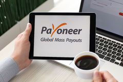 Van het de betalingssysteem van de mensenholding iPad de Prodienst Payoneer op het scherm Royalty-vrije Stock Afbeelding