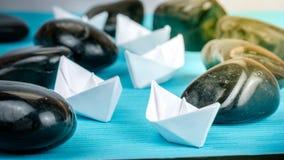 Van het de bootlood van het leidings Witboek de verdere schepen tussen abstracte rotsstenen op blauwe achtergrond De lichte gloed Royalty-vrije Stock Foto